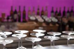 Foto di concetto della barra dell'alcool, vetri al fondo della bottiglia, viola Fotografie Stock