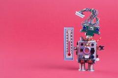 Foto di concetto di previsioni del tempo Meteorologi del robot con il termometro che visualizza temperatura ambiente di comodità  Fotografie Stock