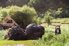 Foto di estate del villaggio di Lokh, Saratov, Russia Un grande mucchio di fieno, un vecchio trattore, una vita del villaggio Immagini Stock Libere da Diritti