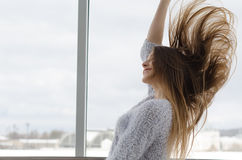 Foto di giovane bella donna sorridente felice con capelli lunghi vicino alla finestra Immagine Stock