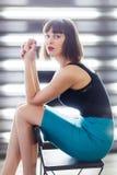 Foto di giovane seduta castana sulla sedia vicino alla finestra con i ciechi fotografia stock libera da diritti