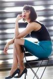Foto di giovane seduta castana sulla sedia vicino alla finestra con i ciechi fotografia stock