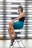 Foto di giovane seduta castana sulla sedia vicino alla finestra con i ciechi fotografie stock
