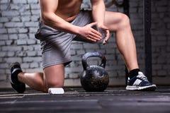 Foto di giovane uomo dell'atleta mentre preparandosi per l'addestramento del crossfit con le teste di legno contro il muro di mat Immagine Stock Libera da Diritti