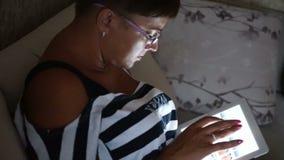 Foto di lettura rapida della giovane donna sul computer della compressa che si trova sul sofà a casa stock footage