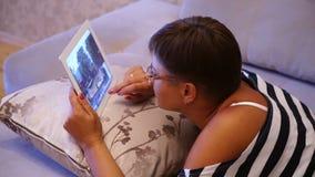 Foto di lettura rapida della giovane donna sul computer della compressa che si trova sul sofà a casa archivi video