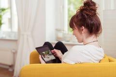 Foto di lettura rapida della giovane donna sul suo compressa-pc Immagine Stock