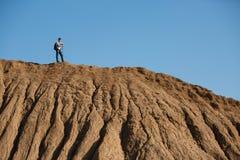 Foto di lontano dell'uomo turistico con i bastoni per la camminata sulla collina contro il cielo blu Fotografia Stock
