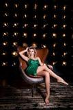 Foto di modo di bella giovane donna in breve vestito elegante, sedentesi su una sedia su un fondo scuro nero con le lampade fotografie stock libere da diritti