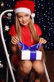 Foto di Natale di piccola ragazza bionda sveglia in cappello di Santa e vestito rosso Fotografia Stock