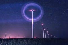 Foto di notte dei generatori eolici e delle stelle con illuminazione astratta Fotografia Stock