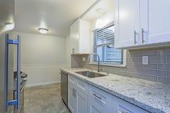 Foto di piccola cucina compatta con i gabinetti bianchi dell'agitatore fotografie stock