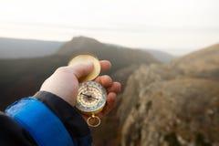 Foto di punto di vista dell'uomo dell'esploratore che cerca direzione con la bussola dorata in sua mano con il fondo delle montag fotografie stock libere da diritti