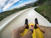 Foto di punto di vista di un uomo che guida giù uno scorrevole alpino in discesa del sottobicchiere su una vacanza di divertiment fotografia stock