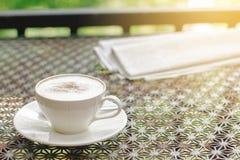 Foto di riserva: Caffè del cappuccino con il giornale sulla tavola d'annata Fotografia Stock Libera da Diritti