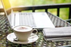 Foto di riserva: Cappuccino con il giornale, il computer portatile o il taccuino sopra Fotografia Stock
