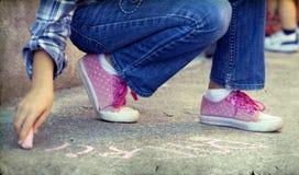 Foto di scrittura del bambino con il gesso sul cortile della scuola fotografia stock libera da diritti