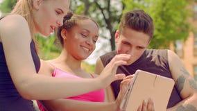 Foto di sorveglianza dei giovani sulla compressa all'aperto Giovani amici che hanno divertimento video d archivio