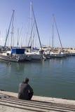Foto di un uomo sul porto marittimo, guardante alle barche a vela Immagini Stock Libere da Diritti