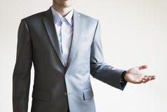 Foto di un uomo in vestito grigio con la presentazione del qualcosa sulla b bianca Fotografie Stock Libere da Diritti
