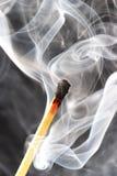 Foto di una corrispondenza burning in un fumo su una priorità bassa nera Fotografie Stock Libere da Diritti