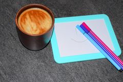 Foto di una tazza di caffè su un fondo di un bordo magnetico e dei pennarelli Un colore saturato del caffè con una schiuma aerata fotografia stock