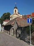 Foto di vecchie vie strette del ciottolo (pietra naturale) della cittadina europea medievale, andanti ad una chiesa cattolica ant Fotografia Stock Libera da Diritti