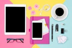 Foto di vista superiore di area di lavoro con derisione dello spazio in bianco sulla compressa e smartphone, tazza di caffè, bloc immagine stock