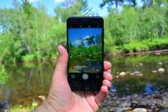 Foto die op smartphone in toeristenreis schieten Nemend rivier een beeld met een slimme telefoon Royalty-vrije Stock Foto