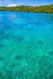 Foto die van de Mens de Natuurlijke Houten Lange Caraïbische Oceaan van de Staartboot drijven Duidelijk water en blauwe hemel met Royalty-vrije Stock Afbeelding