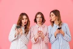 Foto die van drie jaren '20 van vrouwenvrienden kleurrijke gestreepte pyjama dragen Stock Foto's