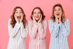 Foto die van drie mooie vrouwenjaren '20 kleurrijke gestreepte pyjama's dragen Stock Afbeeldingen
