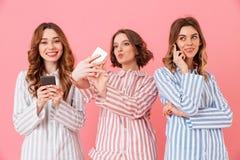 Foto die van drie schitterende jonge meisjesjaren '20 kleurrijke gestreept dragen Royalty-vrije Stock Foto's