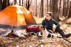 Foto die van een toerist met een hond, in het bos dichtbij de brand en de oranje tent rust stock foto's