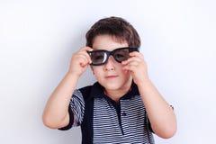 Foto divertente del ragazzino sveglio che mette sugli occhiali da sole, sho dello studio immagine stock