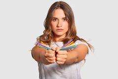 A foto do auto assegurou modelos fêmeas leva palhas coloridas plásticas em ambas as mãos, olha diretamente na câmera, sendo again fotografia de stock
