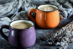 Foto do café no estilo rústico Duas canecas pequenas com uma bebida quente Perto da alfazema Ainda vida em um fundo textured Imagem de Stock Royalty Free