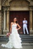 Foto do casamento com noivos Noiva bonita que levanta na perspectiva do noivo e da igreja Católica imagens de stock