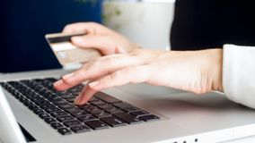 Foto do close up da jovem mulher que paga compras em linha com cartão de crédito imagem de stock royalty free