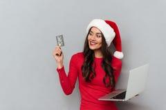 Foto do close-up da mulher moreno bonita no chapéu do ` s de Santa que olha a Fotografia de Stock Royalty Free