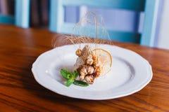 A foto do close-up da parte de gelado com porcas, hortelã e decorado com a laranja secada colocada na tabela de madeira Foto de Stock Royalty Free