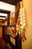 A foto do close-up das cebolas e da grama artificiais que penduram no feixe de madeira no café bonito Imagens de Stock