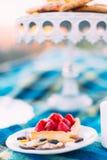 A foto do close-up das cookies do bolo e do chocolade da morango da esponja que encontram-se atrás da placa branca borrada com co Fotos de Stock