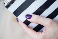 A foto do close-up das mãos manicured do ` s da mulher guarda um caderno elegante com tiras preto e branco foto de stock