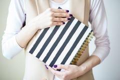 A foto do close-up das mãos manicured do ` s da mulher guarda um caderno elegante com tiras preto e branco fotografia de stock