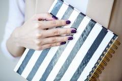 A foto do close-up das mãos manicured do ` s da mulher guarda um caderno elegante com tiras preto e branco fotos de stock