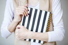 A foto do close-up das mãos manicured do ` s da mulher guarda um caderno elegante com tiras preto e branco imagens de stock