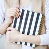 A foto do close-up das mãos manicured do ` s da mulher guarda um caderno elegante com tiras preto e branco foto de stock royalty free