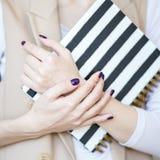 A foto do close-up das mãos manicured do ` s da mulher guarda um caderno elegante com tiras preto e branco imagem de stock royalty free
