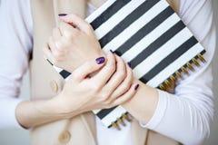 A foto do close-up das mãos manicured do ` s da mulher guarda um caderno elegante com tiras preto e branco fotografia de stock royalty free
